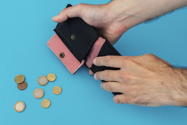 Mãos masculinas com um close de carteira vazia. moedas de euro em um fundo azul