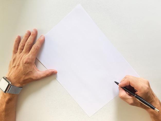Mãos masculinas com uma caneta sobre a folha de papel