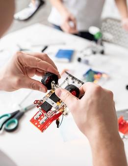 Mãos masculinas construindo carros-robôs na oficina