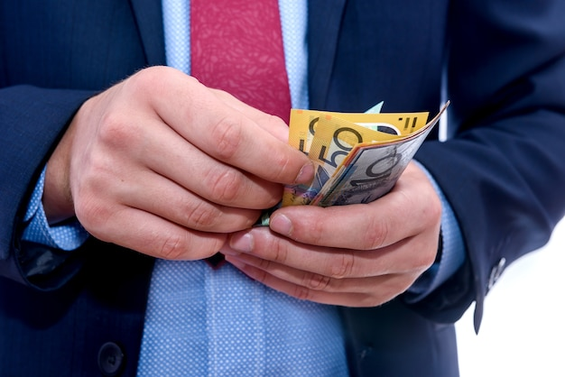 Mãos masculinas contando notas de dólar australiano de perto