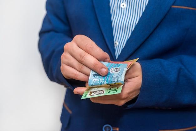 Mãos masculinas contando notas de dólar australiano