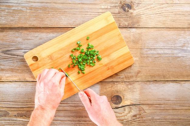 Mãos masculinas cortam uma cebola verde em uma placa de corte