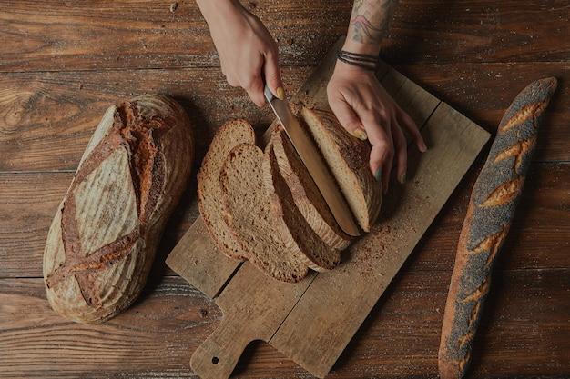 Mãos masculinas cortando pão caseiro em um fundo de madeira