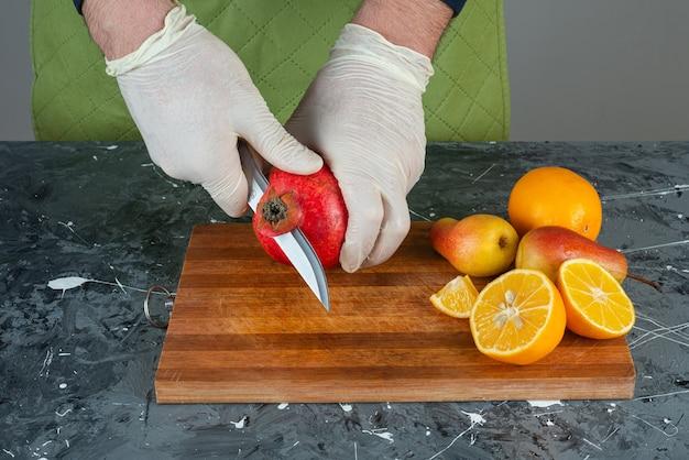 Mãos masculinas cortando romã vermelha na mesa de mármore.