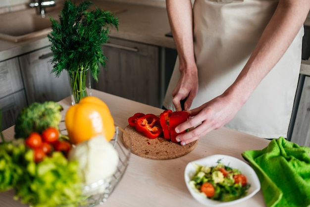 Mãos masculinas cortando uma cebola, cozinhando alimentos saudáveis na cozinha.