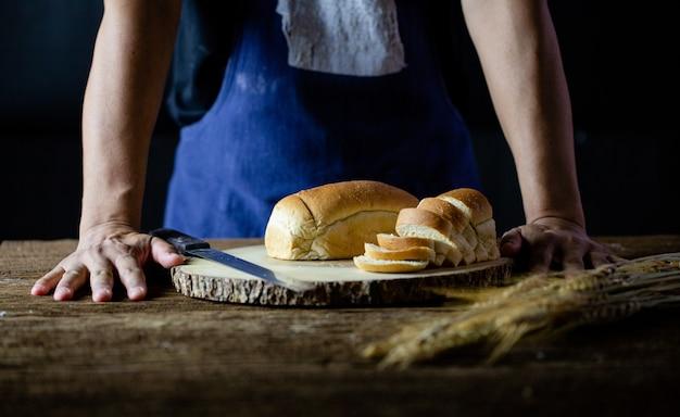 Mãos masculinas, corte o pão de trigo na placa de madeira. pão tradicional cortado em fatias