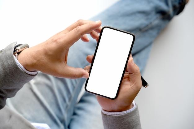 Mãos masculinas da vista superior usando o smartphone no fundo borrado.