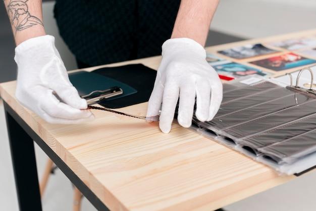 Mãos masculinas de close-up, trabalhando com fotos em um estúdio