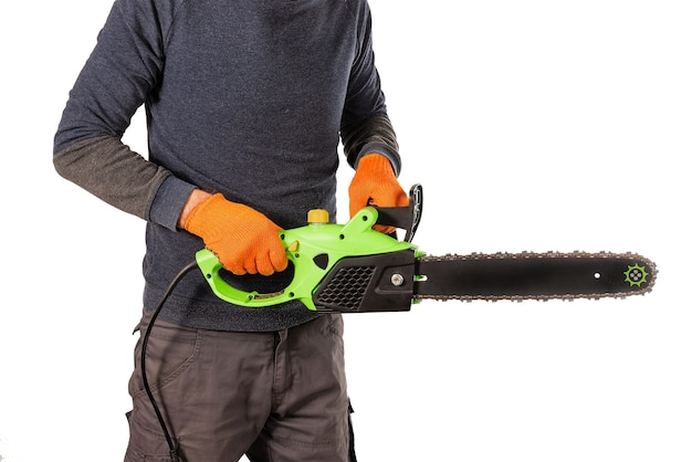 Mãos masculinas de serrador em luvas de proteção têxtil laranja carregam uma nova serra elétrica