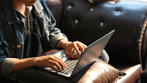 Mãos masculinas de tiro cortadas digitando no teclado do laptop enquanto está sentado no sofá na sala vintage.