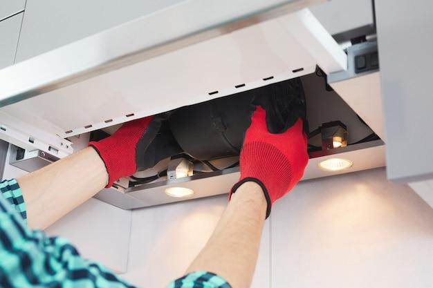 Mãos masculinas de um eletricista solucionam o problema de um exaustor. reparação do exaustor.