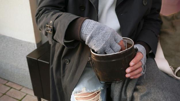 Mãos masculinas de um velho sem-teto segurando uma tigela, um copo de doações