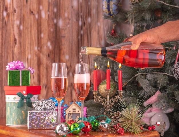 Mãos masculinas derramando champanhe de uma garrafa em champanhe tremulam no contexto de uma árvore de ano novo e presentes.