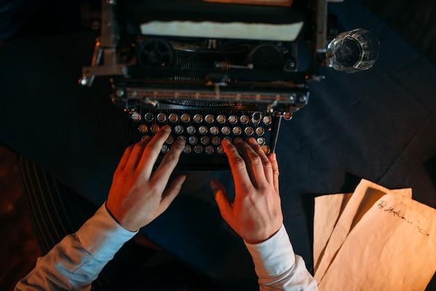 Mãos masculinas digitando em uma máquina de escrever retrô