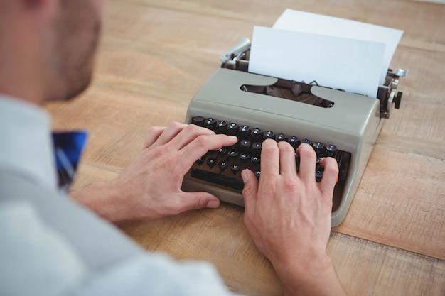 Mãos masculinas digitando na velha máquina de escrever na mesa de madeira