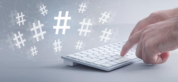 Mãos masculinas digitando no teclado do computador. hashtag. mídia social