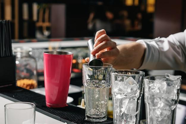 Mãos masculinas do barman, faz um cocktail no bar, copos com gelo.