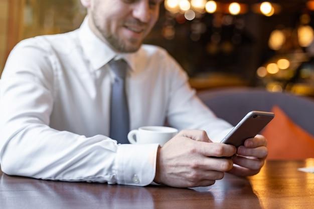 Mãos masculinas do close up que guardam um telefone celular. concentre-se no celular. fundo desfocado
