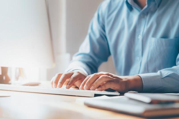 Mãos masculinas do close up usando o computador.