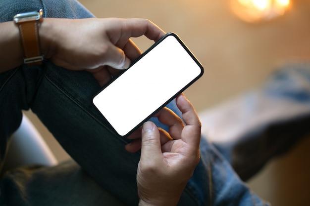 Mãos masculinas do close up usando o smartphone móvel no fundo borrado da noite.