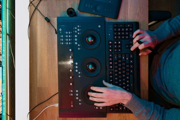 Mãos masculinas do editor de vídeo funcionam com filmagem ou vídeo no painel de controle do computador pessoal, ele trabalha no creative office studio ou em casa. luzes de neon