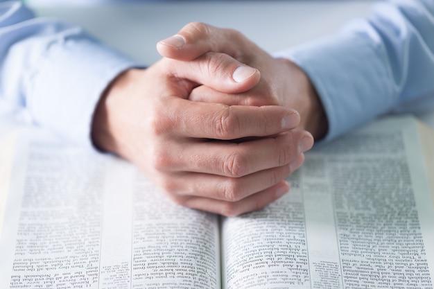 Mãos masculinas e a bíblia sagrada no fundo