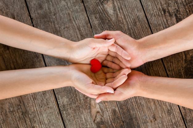Mãos masculinas e fêmeas que guardam o coração vermelho no fundo de madeira.
