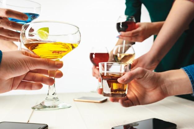 Mãos masculinas e femininas com cocktails exóticos