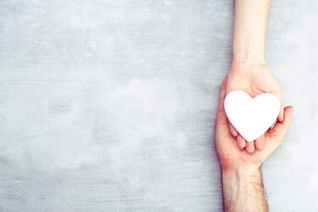 Mãos masculinas e femininas com um coração branco, cuidados de saúde, amor e conceito de seguro familiar