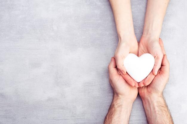 Mãos masculinas e femininas com um coração branco, cuidados de saúde,