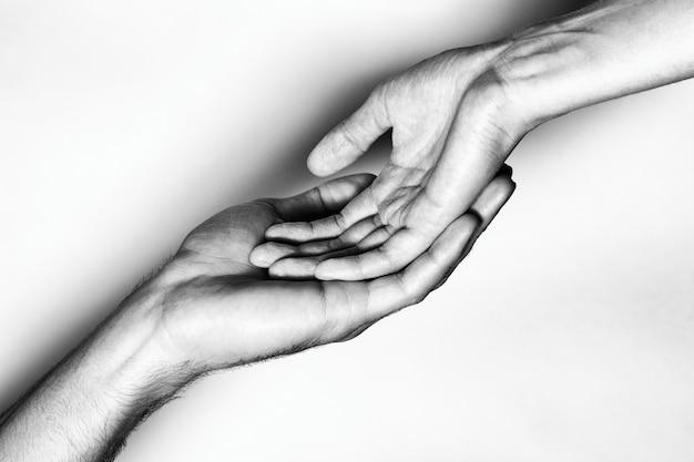 Mãos masculinas e femininas juntas. a foto em preto e branco