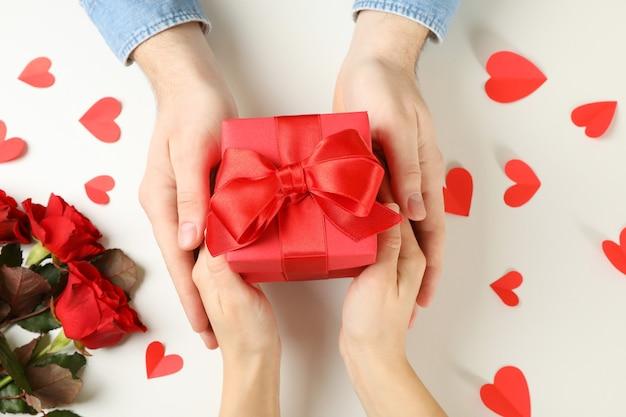 Mãos masculinas e femininas segurando uma caixa de presente em fundo branco com corações e rosas