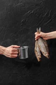 Mãos masculinas e femininas segurando uma caneca de metal e uma barata seca com sal