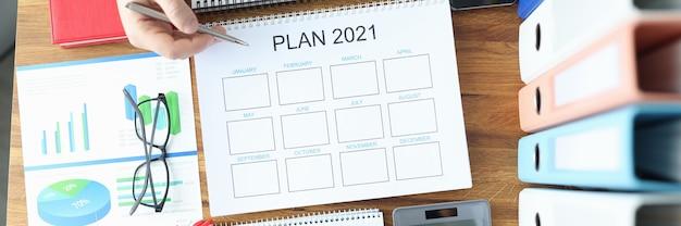 Mãos masculinas e femininas segurando uma caneta esferográfica com documentos com plano para 2021 na mesa do escritório
