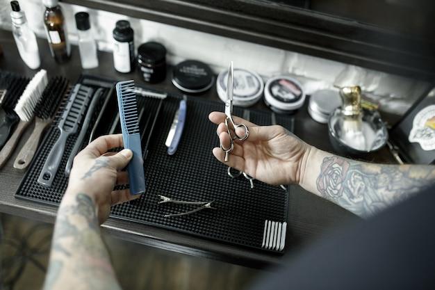 Mãos masculinas e ferramentas para cortar a barba na barbearia. ferramentas vintage de barbearia.