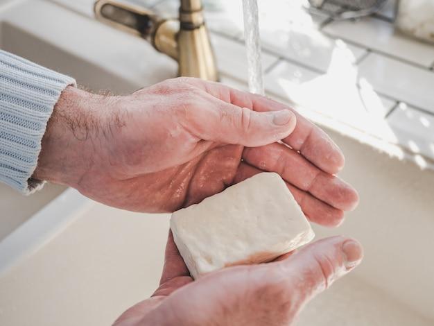 Mãos masculinas e uma barra de sabão