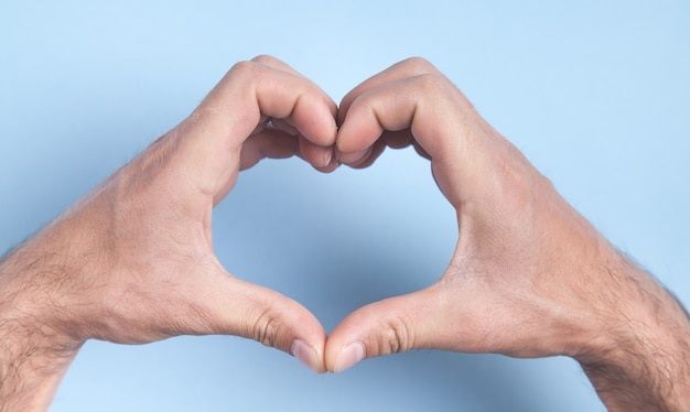 Mãos masculinas em forma de coração.