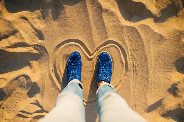 Mãos masculinas em jeans azul e tênis elegantes em pé dentro pintado coração na areia.