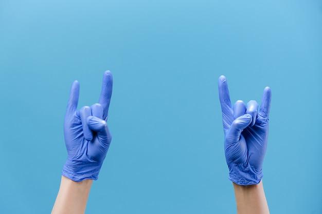 Mãos masculinas em luvas acenando com gesto de chifres