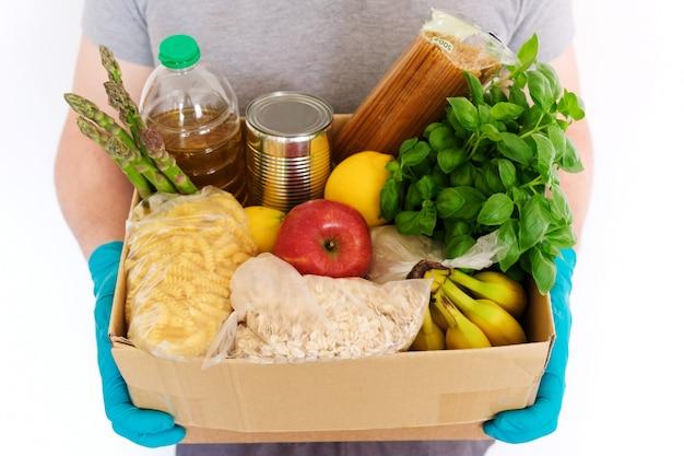 Mãos masculinas em luvas médicas de borracha segura uma caixa de papelão com produtos. óleo de girassol, conservas, massas, aveia, arroz, legumes e frutas. entrega a domicílio, doação de alimentos