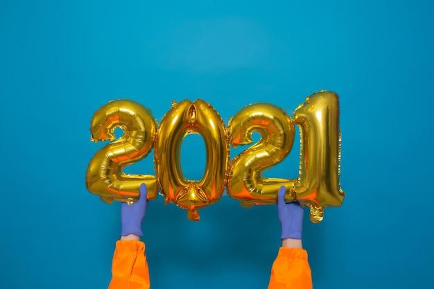 Mãos masculinas em luvas médicas segurando balões dourados com os números 2021
