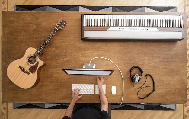 Mãos masculinas em um computador em uma mesa de madeira com um violão, teclas musicais e fones de ouvido de estúdio.
