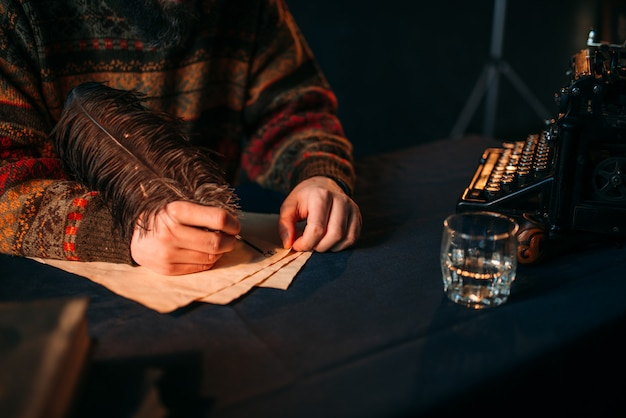 Mãos masculinas escrevendo com uma pena em papel vintage