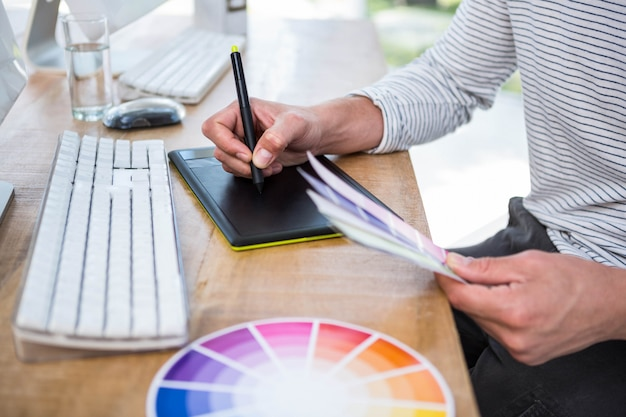 Mãos masculinas, escrevendo em tablet digital em um escritório brilhante