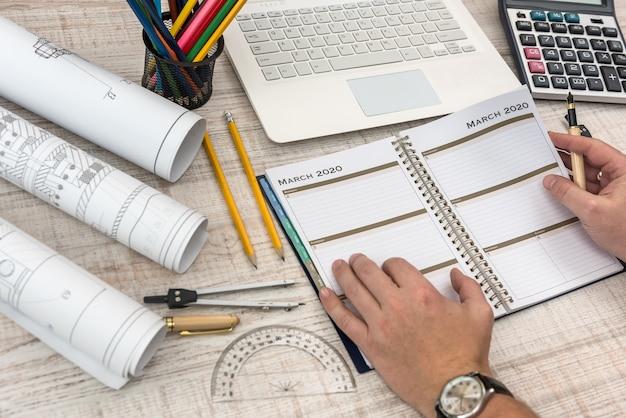 Mãos masculinas, escrevendo no bloco de notas com parte do projeto industrial com calculadora, ferramentas e laptop.
