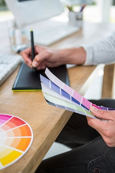Mãos masculinas, escrevendo no tablet digital sobre amostras de cores em um escritório brilhante