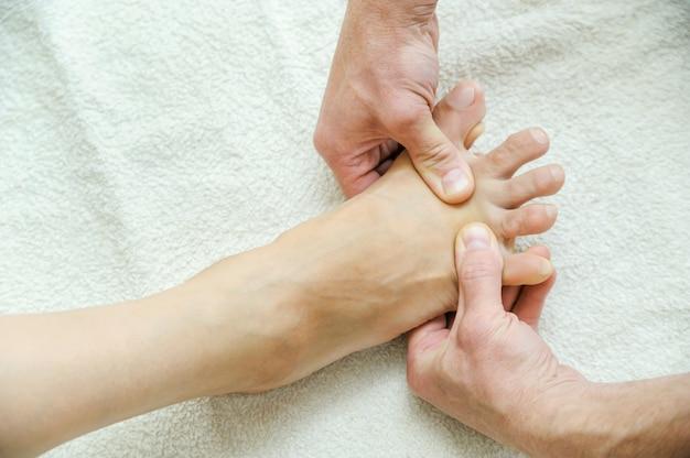 Mãos masculinas estão massageando os pés.