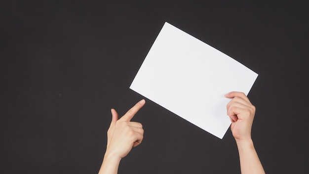 Mãos masculinas estão segurando e apontam o dedo para o papel a4 em fundo preto.
