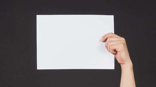Mãos masculinas estão segurando o papel a4 em fundo preto.