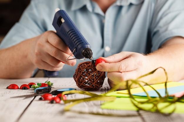 Mãos masculinas fazem decoração artesanal com cola